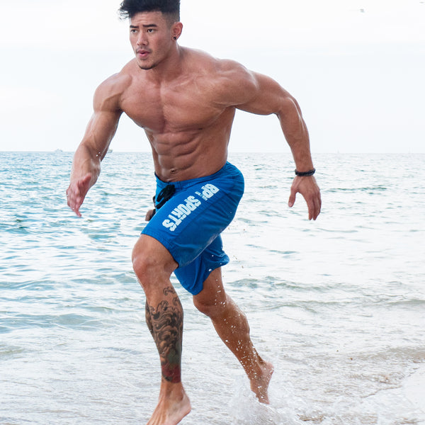 Man running down the beach in the blue BPI Sports Swim Trunks