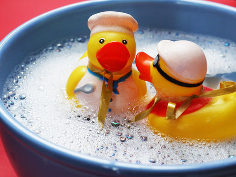 Two rubber ducks swimming in bubble water
