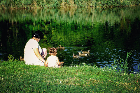 Mom and baby sitting by lake watching ducks