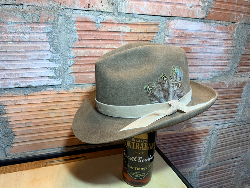 Fedora hat pictured in Pecan with a velvet hatband and custom feather embellishment.