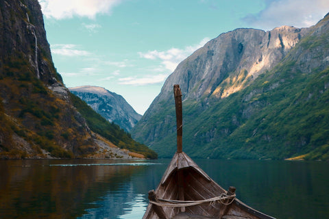 Viking drakar boat on a Scandinavian lake in either Denmark, Norway or Sweden. Mountains in the background.