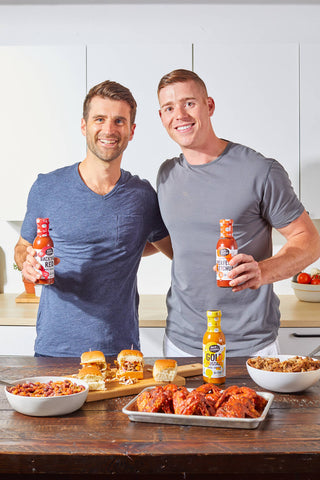 Matt and Rob of Halo + Cleaver smiling together with their bottled sauces