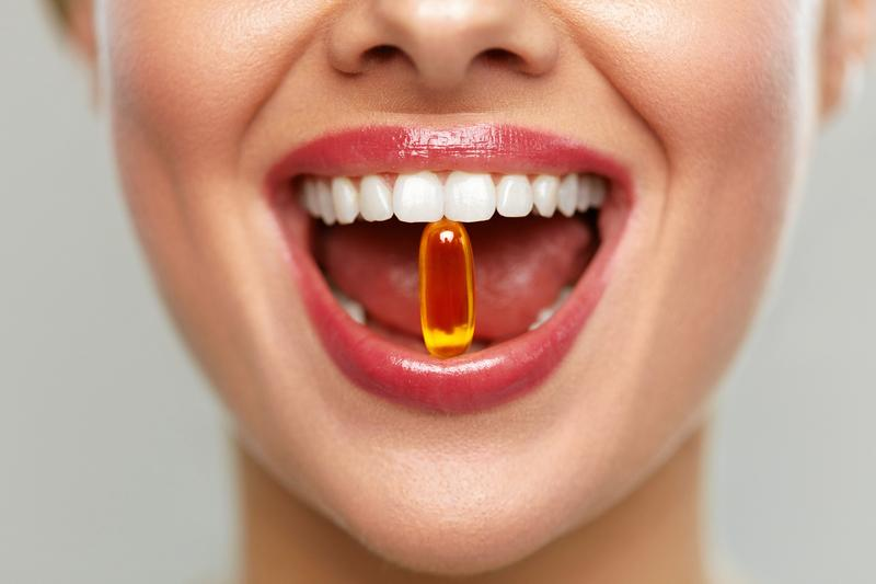 Woman smiling with vitamin between her teeth