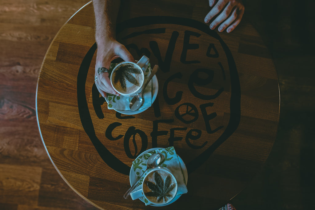 Two coffee cups with a weed leaf inside sitting on top of a wooden, hippie-style table that says peace love and coffee to make weed coffee
