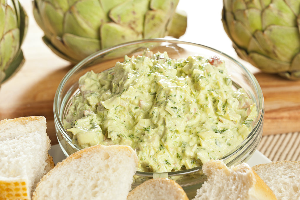 Bowl of artichoke dip with artichokes and bread slices