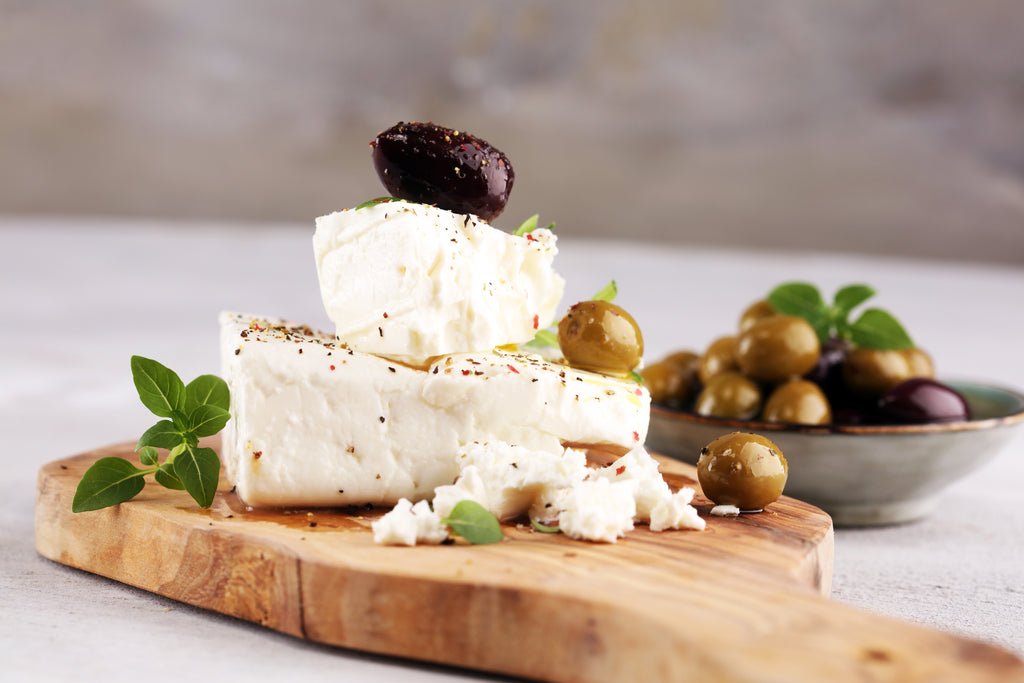 Goat cheese and olives on a cutting board