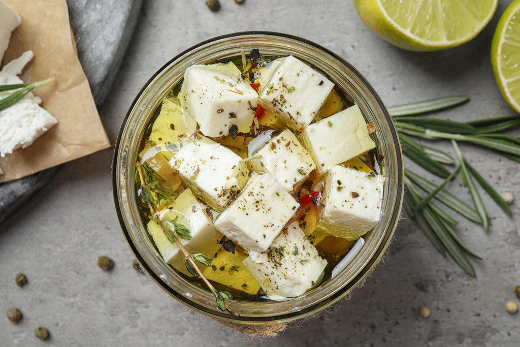 goat cheese marinating in a jar with spices and Pantry evoo