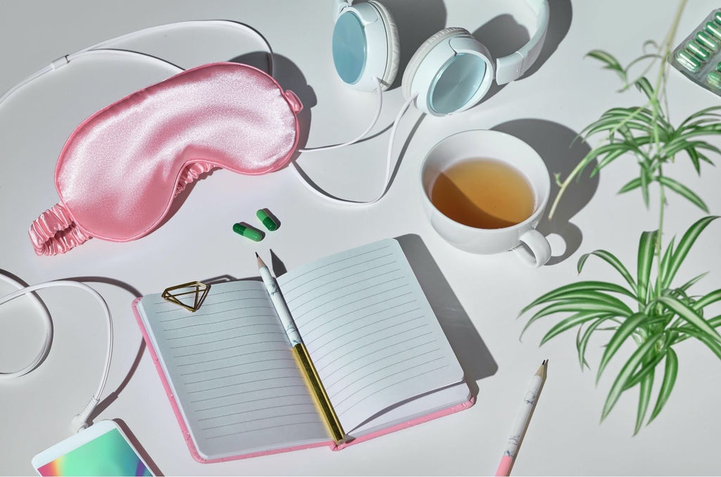 photo of journal, pink sleep mask, heaphones and tea signifying examples of some daily rituals