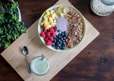 Bowl of raspberries, blueberries, granola, and other healthy ingredients on top of a wooden cutting board next to a cup of fruit to promote healthy cannabis-infused eating