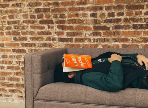 Middle-aged man in dark long sleeve shirt resting on a gray couch in front of a red brick wall after consuming cannabis for sleep with a book on his face about hacking growth boasting a bright orange cover
