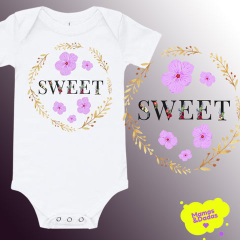 "White baby bodysuit with floral elements as a design in front. The word ""Sweet"" with black letters is in the middle of a wreath, made by flowers and branches."