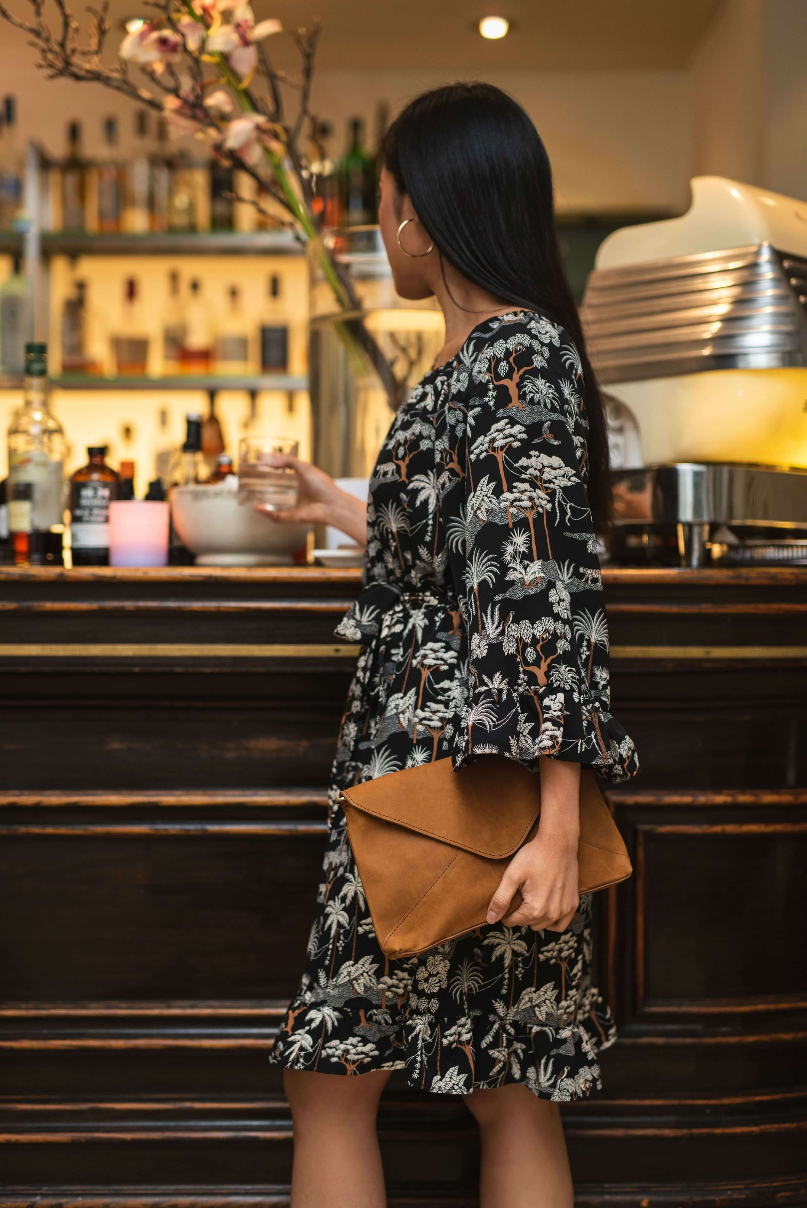 Madrid Tan Leather Envelope Pouch cross body bag with model at a bar