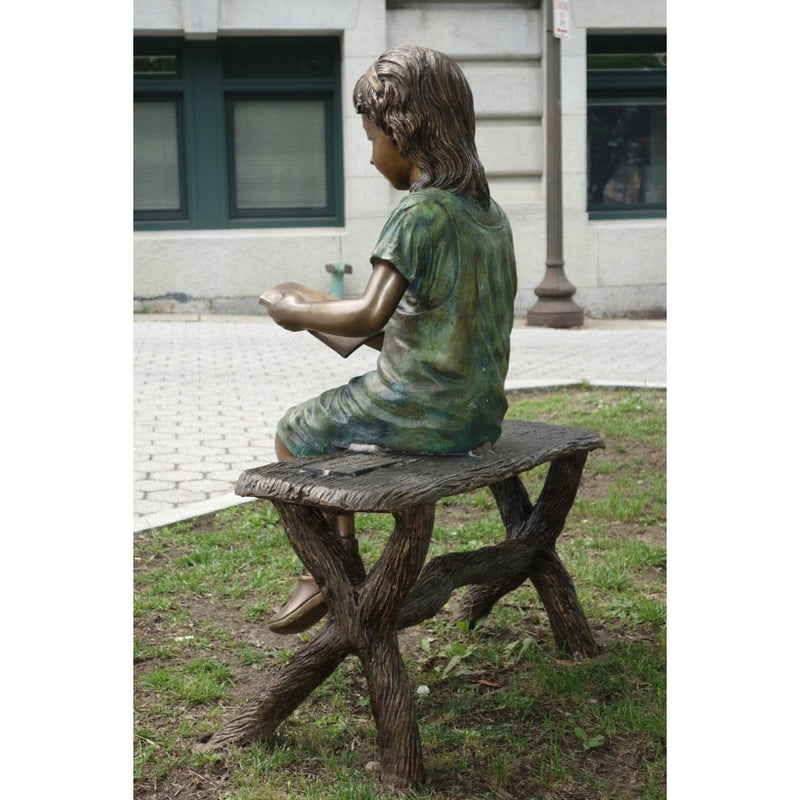 Bronze Statue of a Girl Reading a Book on a Bench