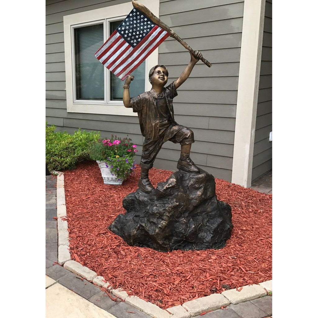 patriotic bronze statue of boy  holding the american flag