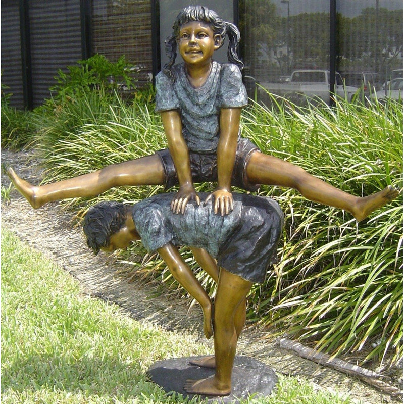 children playing leap frog bronze statue