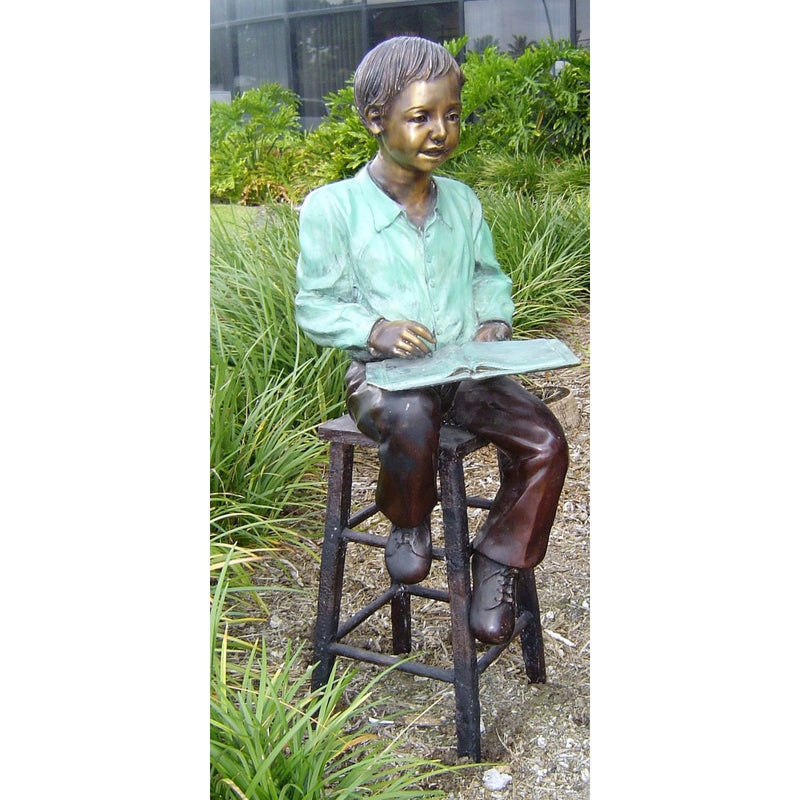 Bronze Statue of Boy Reading a Book Sitting on a Stool