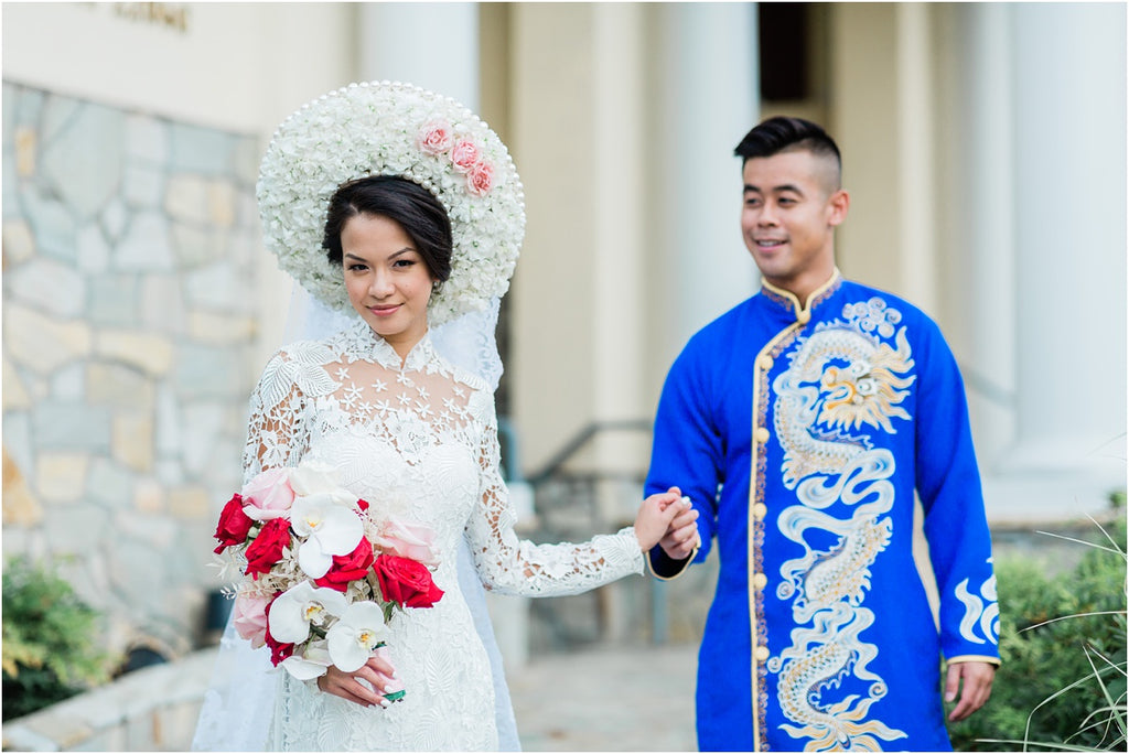 A Vietnamese bride wearing a white ao dai and groom hold hands