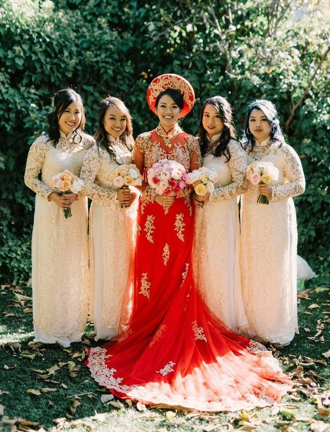 Vietnamese bride in a red and gold áo dài with her bridesmaids in soft pink áo dài.