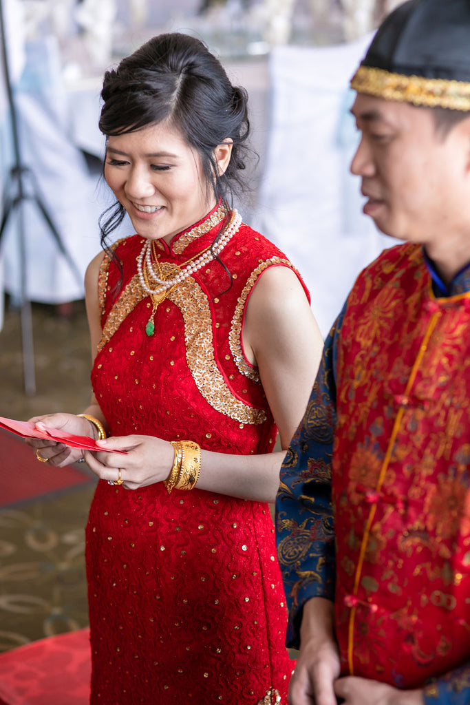 Asian bride wearing red and gold cheongsam