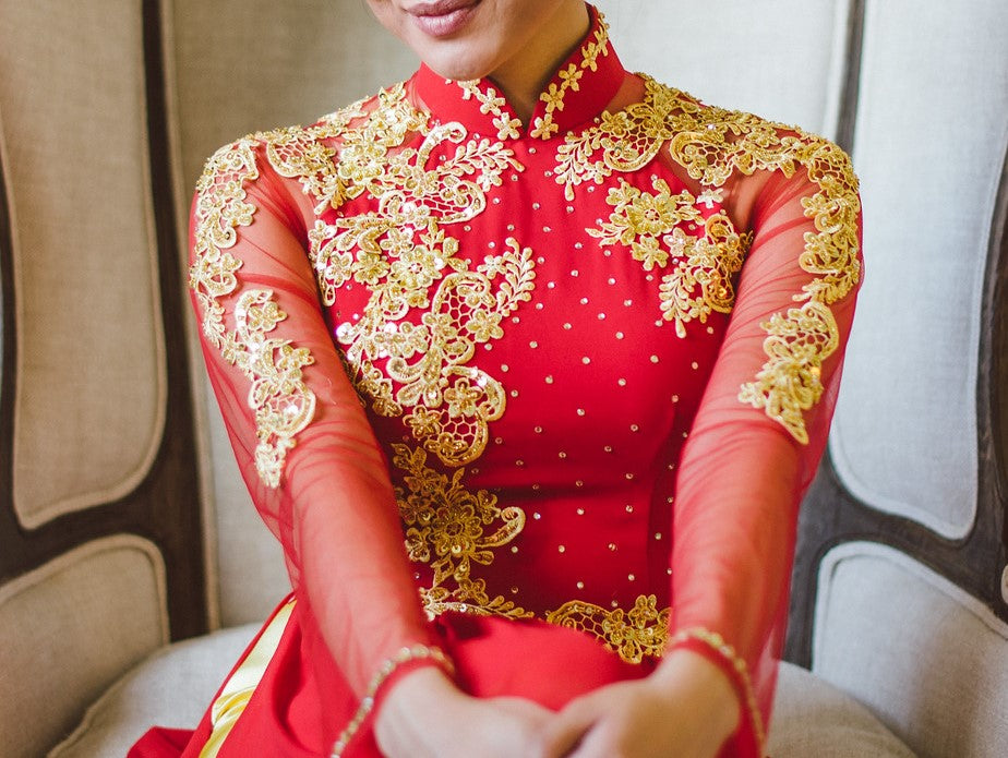 Close up of a Vietnamese bride wearing a red áo dài embroidered with gold lace on the bodice, sleeves, and mandarin collar.