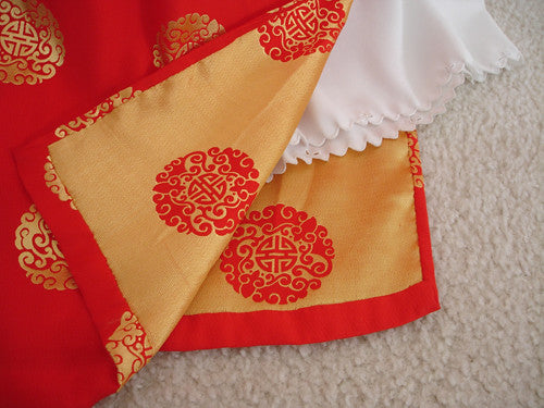 Close up of an ornate red and gold patterned brocade with white trouser fabric.