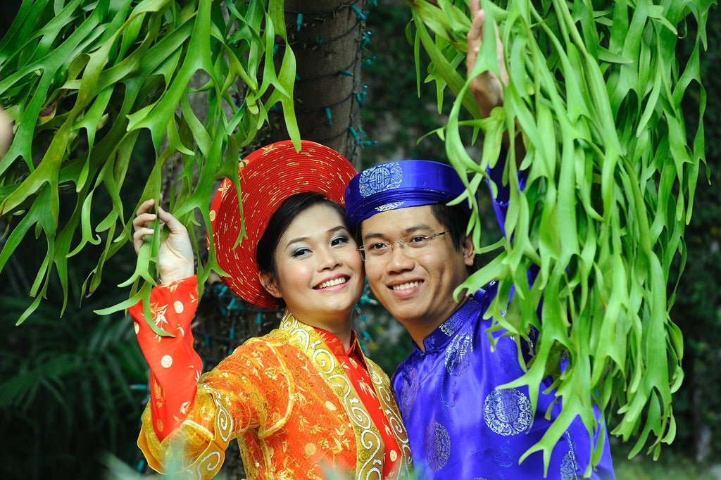 Vietnamese bride and groom in different colored áo dài with matching khăn đóng in their respective brocade fabric.