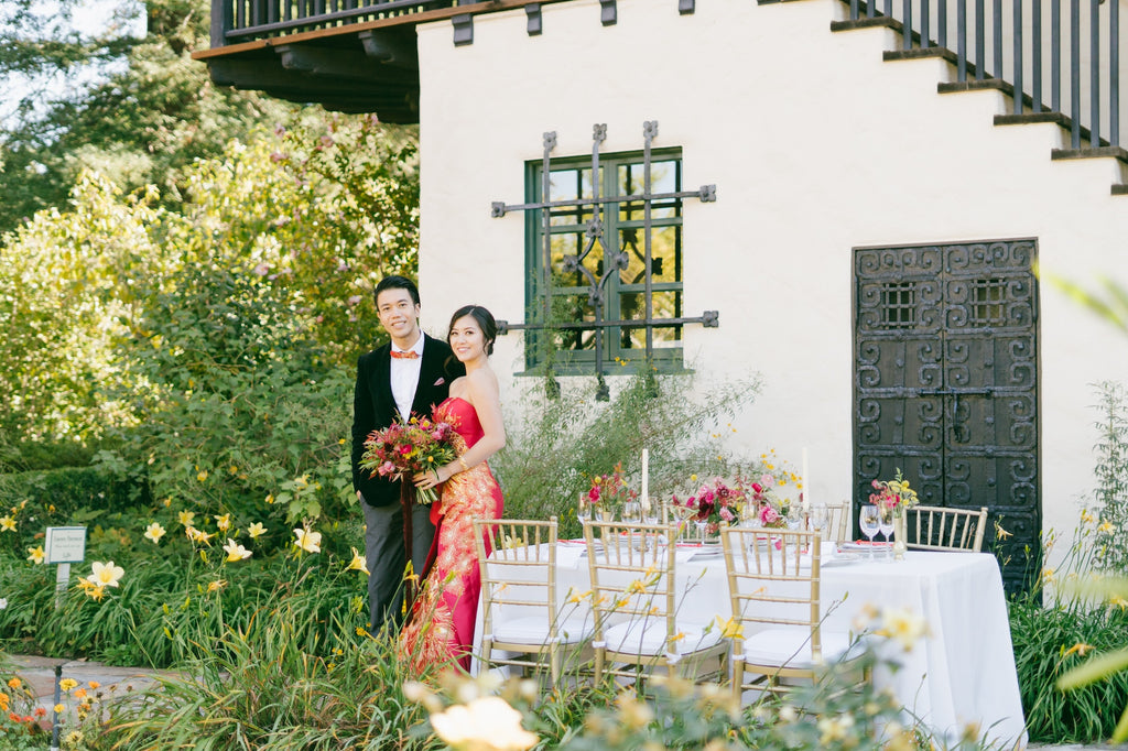 A newlywed couple standing in a garden.