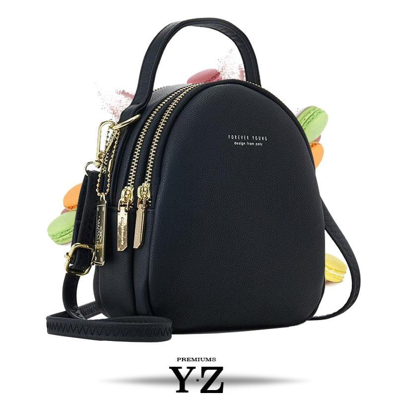 Bold and elegant, the Macaron Collection is one of our favorites. Made with soft, smooth faux-leather, it features a modern, versatile design that styles up any outfit with effortless elegance. The luxurious golden zippers and tags create a stunning accent against the classy body. Spacious and practical in its design, this cross-body strapped shoulder bag is perfect for carrying your essentials as you head out for an evening filled with fun, excitement, and adventure.