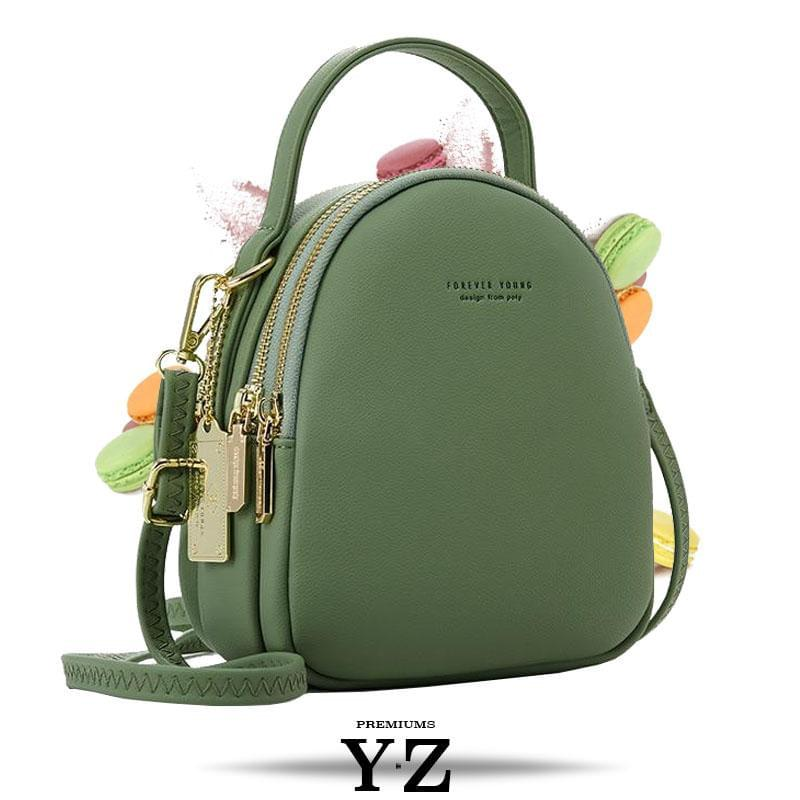 Bold and elegant, the green macaron is one of our favorites. Made with soft, smooth faux-leather, it features a modern, versatile design that styles up any outfit with effortless elegance. The luxurious golden zippers and tags create a stunning accent against the classy green body. Spacious and practical in its design, this cross-body strapped shoulder bag is perfect for carrying your essentials as you head out for an evening filled with fun, excitement, and adventure.