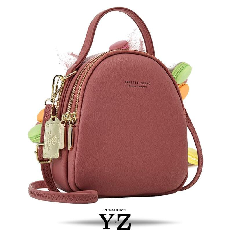 Bold and elegant, the wine red macaron is one of our favorites. Made with soft, smooth faux-leather, it features a modern, versatile design that styles up any outfit with effortless elegance. The luxurious golden zippers and tags create a stunning accent against the classy red body. Spacious and practical in its design, this cross-body strapped shoulder bag is perfect for carrying your essentials as you head out for an evening filled with fun, excitement, and adventure.