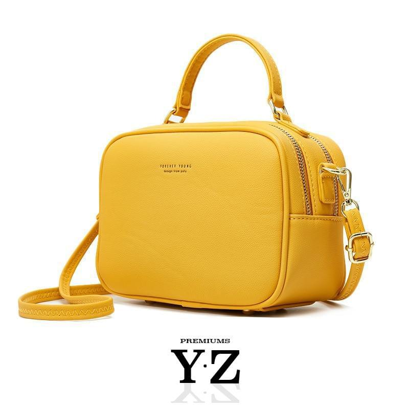 "The Signature Handbag has four points in the bottom that ensure a well-balanced bag when not holding the bag. Gold-colored zippers create a shiny style hidden in the details. With a font ""Young Forever"" with the same color tone as the zippers, gives us the message that stylish Signature handbag is adaptable regardless of age and experience. Inside, we find two equally large pockets in the handbag that offer very good space for everything one would need for an important and charming occasion."