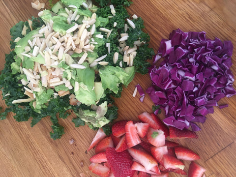 image of kale, avocado, strawberries, slivered almonds and red cabbage chopped