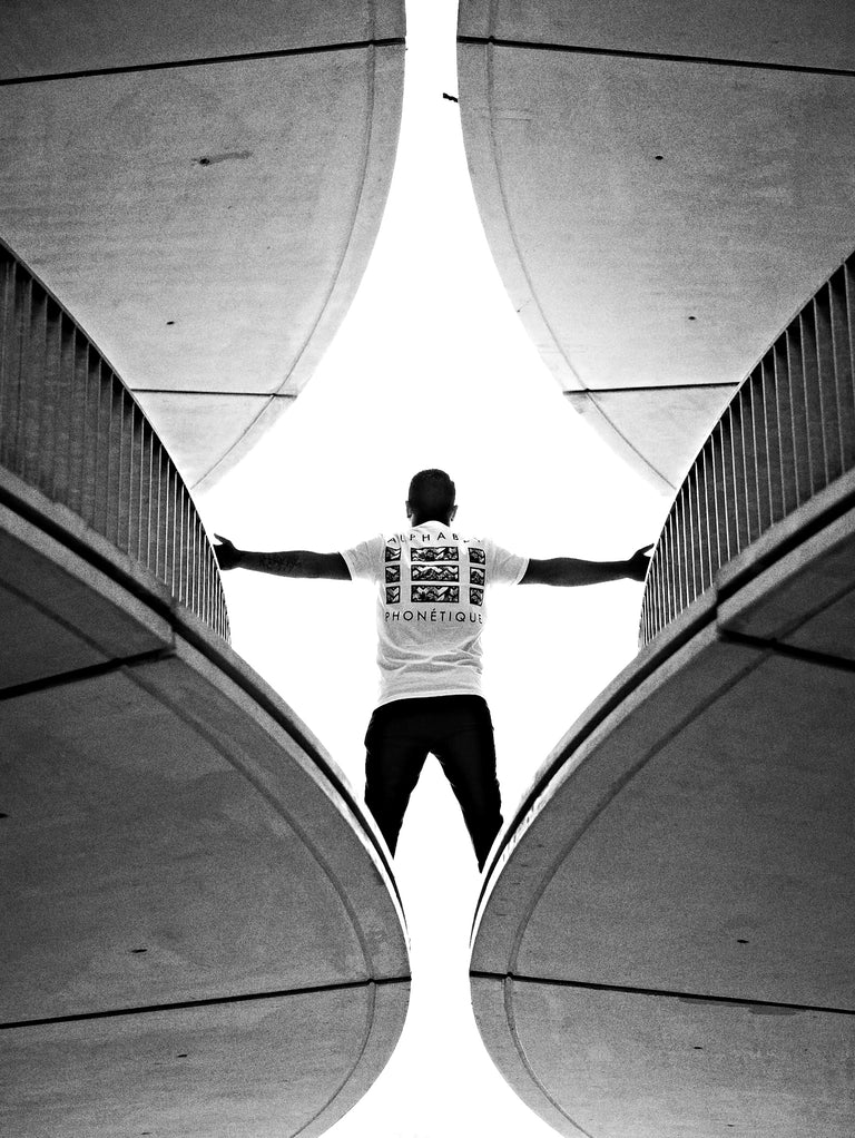 man wearing white Alphabet Phonétique wallflower t-shirt standing in symetric building with his arms spread out