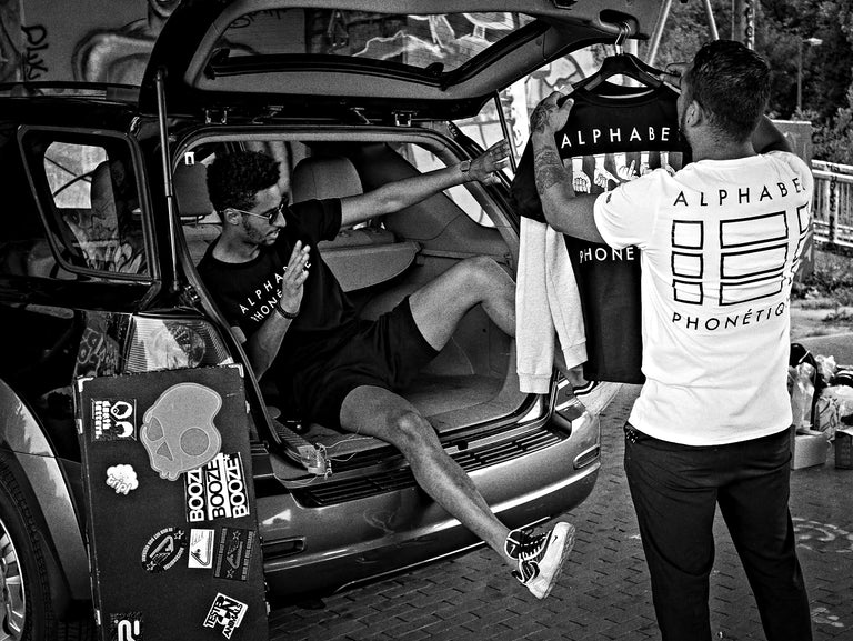 Two men in Aphabet Phonetique shirts behind a parked car