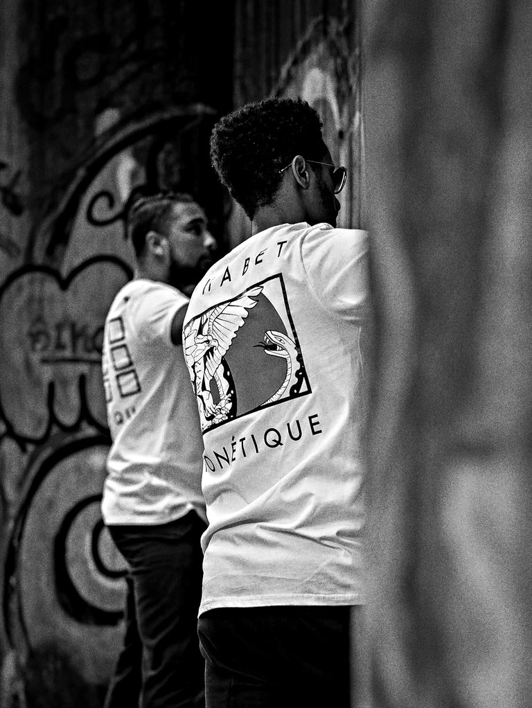 two men wearing Alphabet Phonétique shirts spraying graffiti on wall