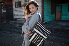 Load image into Gallery viewer, Black and white striped backpack with an exterior zip pocket. Lightly cushioned leather straps, top zipper, and interior welt pocket.