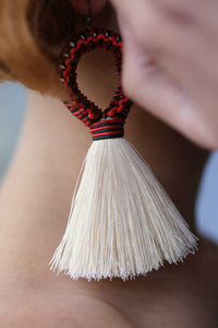 Handmade earrings with black and red loop and white tassel detail made from recycled cotton