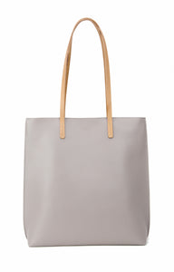 Grey vegan leather tote bag with beige colored lining and one internal pocket.