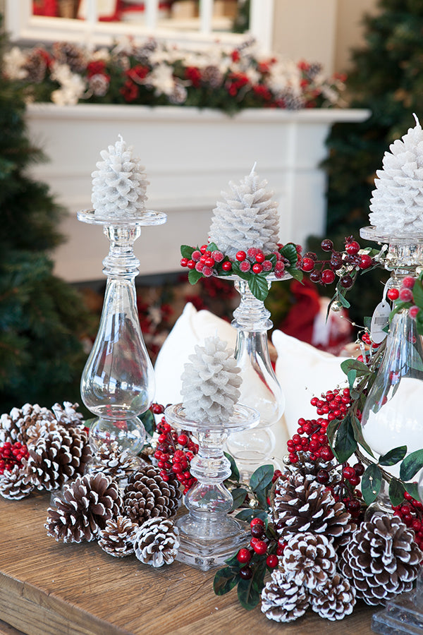 Glass candle holders with pinecones.