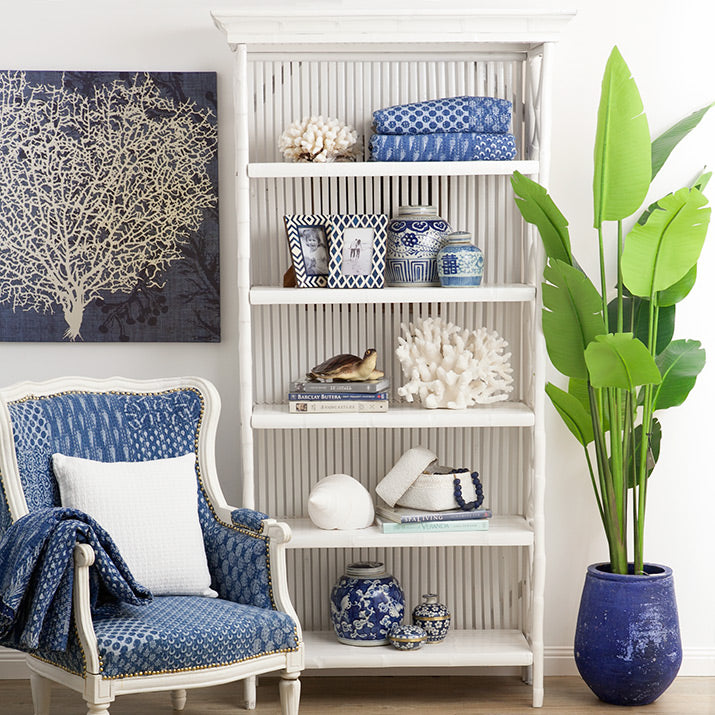 White bamboo bookcase styled with blue and white accessories.
