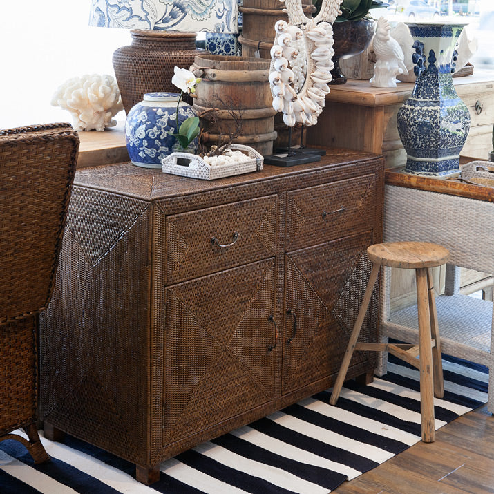 Brown rattan cabinet with blue and white decor.