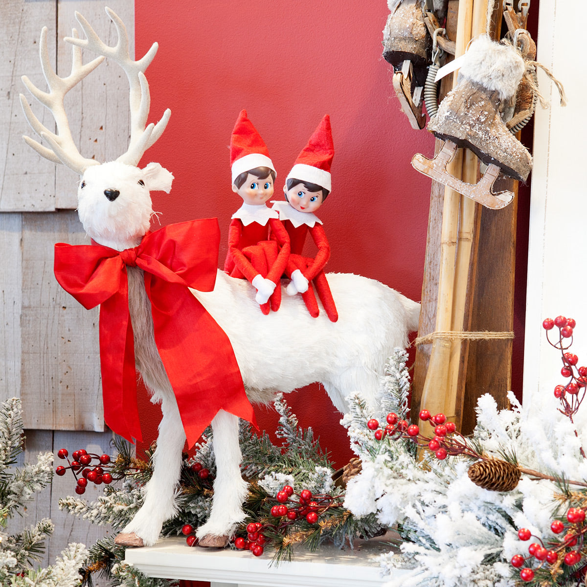 Two elves ride a reindeer in our shop.