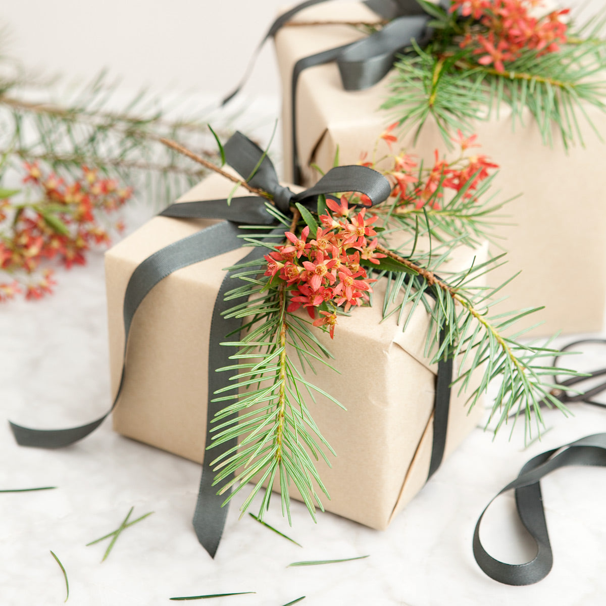 Gifts wrapped in brown paper with foliage and grey ribbon.