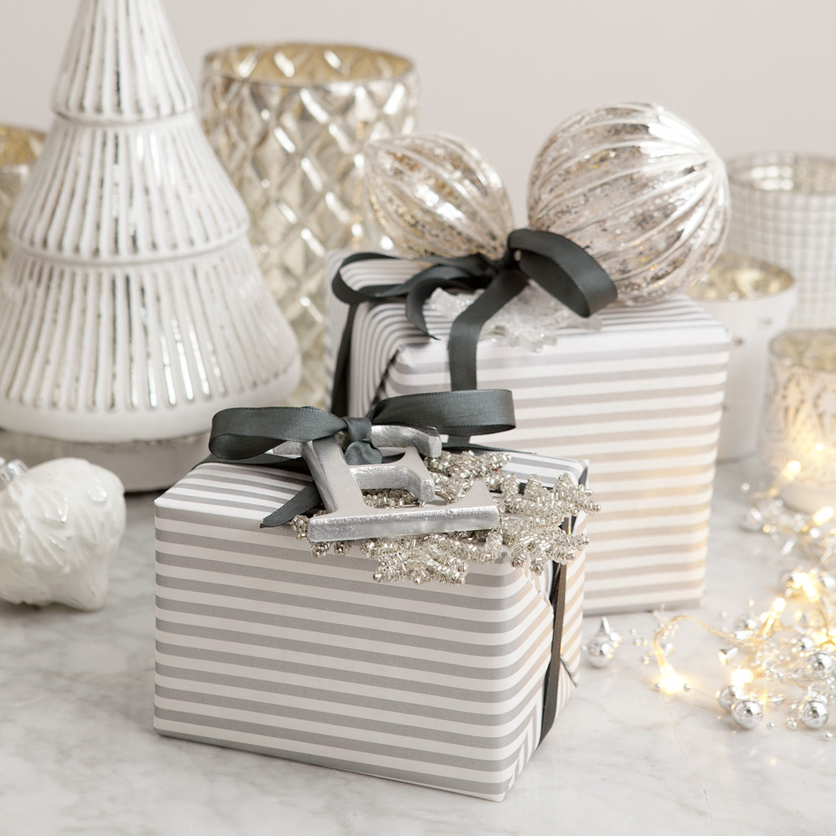 Gifts wrapped in silver and white with glass decorations.
