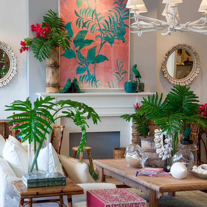 A lounge room filled with green foliage and a large pink artwork.