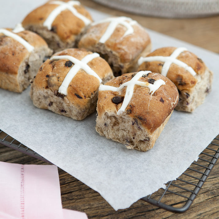 Hot Cross Buns cool down on a baking tray.
