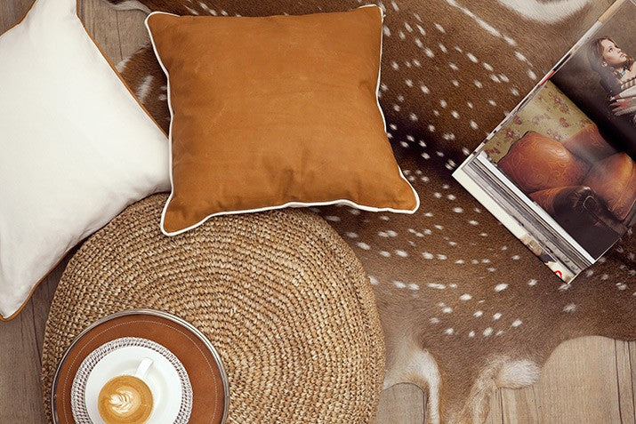 Leather cushion, deer hide and raffia.