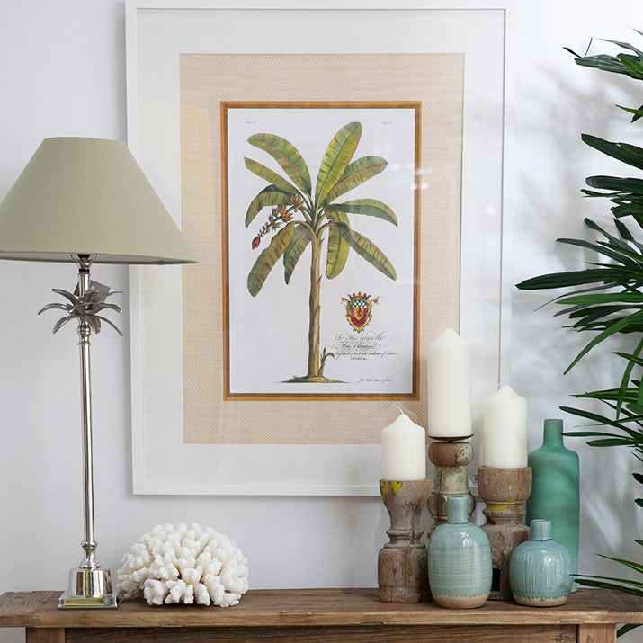 Palm print and lamp with rustic candle holders.