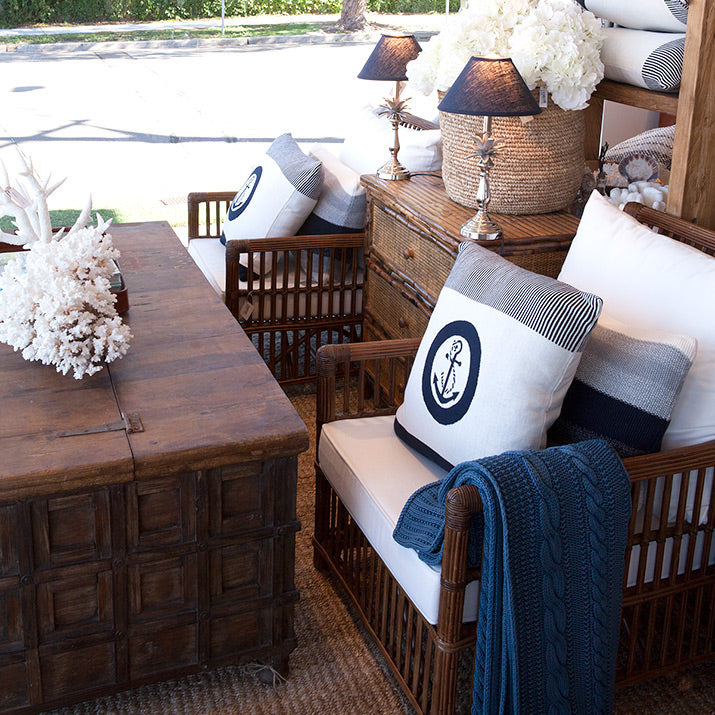Carved Indian chest used as coffee table with rattan armchairs.