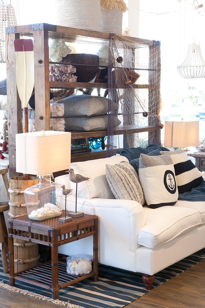White nantucket lounge with anchor cushion and rattan side table.